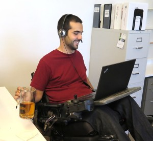 Link to Employment and Benefits; image of a young man in a wheelchair speaking into his headset and looking at his laptop
