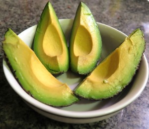 Link to Health and Wellness; image of a bright green avocado, sliced into four quarters