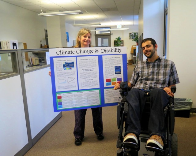 A woman holds a colorful poster board about climate change while a young man in a wheelchair gestures at it, smiling