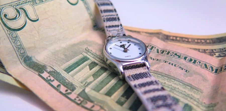 A small, black and white watch rests on a five dollar bill