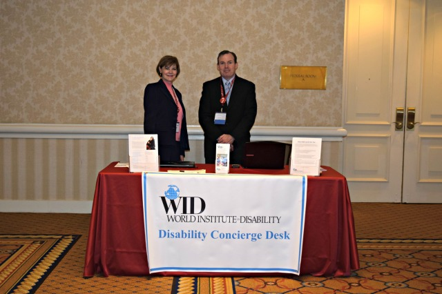 Link to JPMorgan Chase Kicks Off New Conference Accessibility Inititiative article; image of two WID staff members standing behind an accessibility desk in a hotel lobby