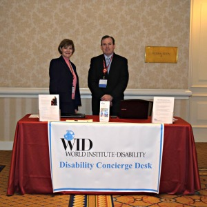Link to Conference Accessibility Initiative; image of two WID staff members standing behind WID's accessibility desk