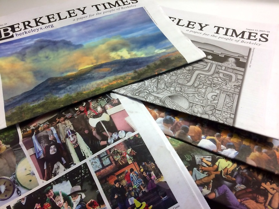 Several different Berkeley Times newspapers are piled up on a table