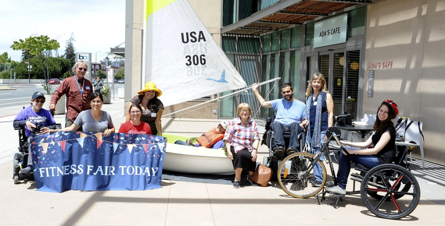 A group of ten people sit around an adaptive sailboat and an adaptive bike