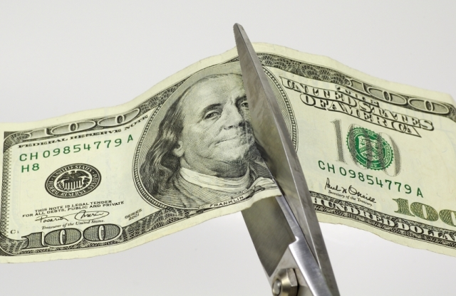 Link to Congress Agrees to a Spending Bill That Cuts AFI article; image of a pair of scissors slicing through a $100 bill