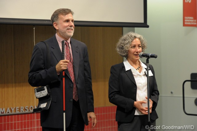 A woman speaks into a microphone while a man stands behind her and smiles at the crowd