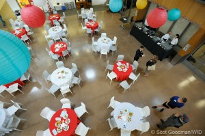 Several tables with red and white alternating table cloths and white chairs