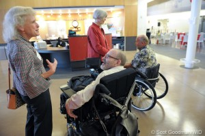 Two men in wheelchairs talk to two women near the front doors