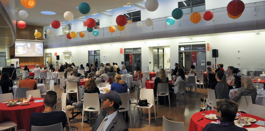 The atrium of the Ed Roberts Campus, full of people sitting around brightly covered tables, eating and talking
