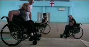 Participants of a Georgian mobility workshop navigating a ramp obstacle.