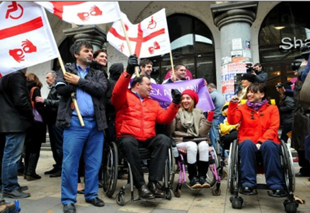 A small crowd of people, many in wheelchairs, raise red and white disability flags in the air.