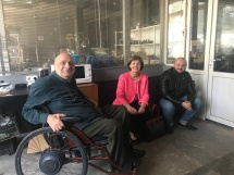3 smiling people, one in a wheelchair and two on a couch