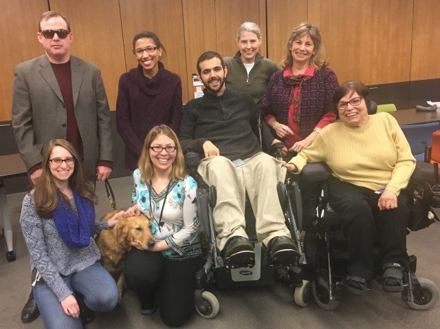 Seven WID staff members and one service dog pose with Judy Heumann, WID co-founder