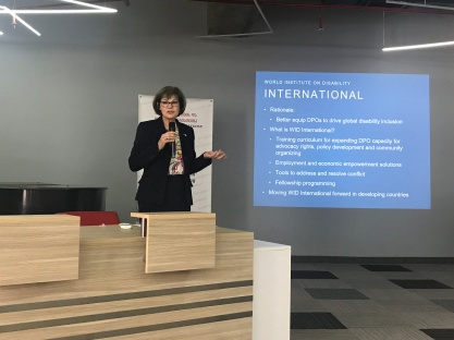 "A woman wearing glasses and a black suit speaks into a microphone and gestures in front of a PowerPoint presentation titled ""World Institute on Disability International"""