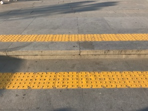 Two wide stone steps with yellow truncated dome tactile paving