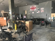 A room full of wheelchairs with a Georgian flag hung on the wall