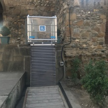 A glass and metal wheelchair lift built in to a stone church's exterior entrance.