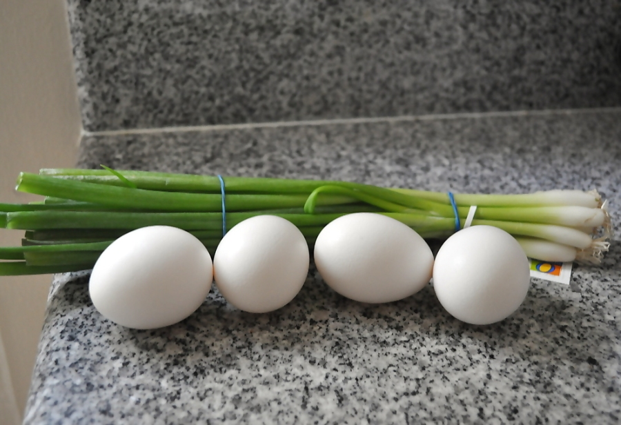 Four eggs and a bunch of green onions