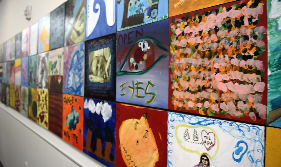 A wall of tiles, painted with disability themes