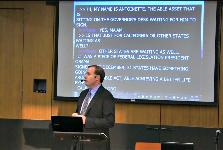 In a suit and tie and in front of an audience, WID's Deputy Director, Tom Foley, presents about ABLE accounts