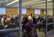 Many people with disabilities in a room, turned toward the speaker and the three screens with captioning
