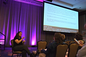An ASL interpreter sits in the front of the room near a screen of open captions