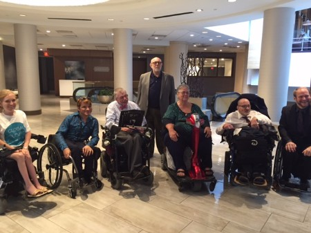 A group of seven, six people in wheelchairs, all smiling