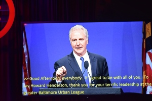 A man speaks into a microphone, open captions below him