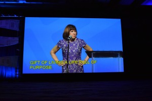 A woman stands against a blue background, hands on her hips, yellow captions beneath her