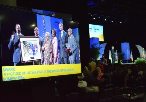 Six people stand on stage with a large photograph, open captions play on the screen
