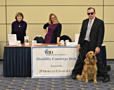 Three WID staff members and one service dog stand in front of a desk