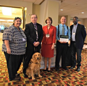 Five people with varied disabilities and one service dog