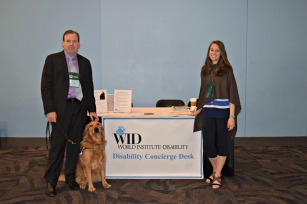 Two people and a service dog stand beside a desk