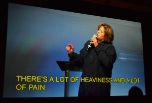 A woman in black speaks dramatically into a microphone, yellow captions beneath her
