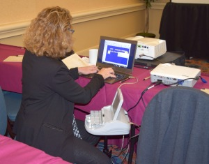 A woman leans over her laptop, a stenograph to her right