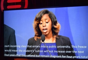 A young woman speaks into a microphone, open captions below her
