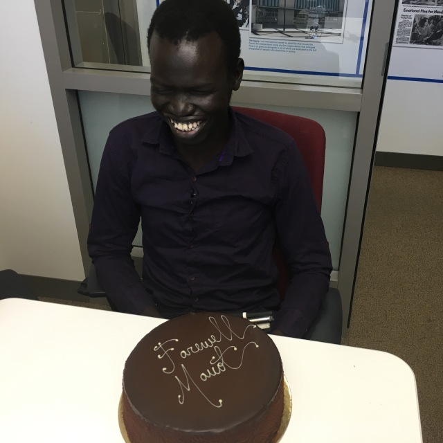 A man smiles, a chocolate cake on the table in front of him