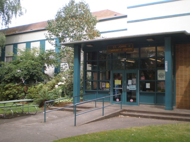 The front of St. John's community center in Portland, Oregon. This building has a ramp with handrails and green plants out front.