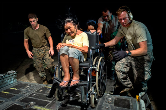 An elderly Filipina woman sitting in a manual wheelchair is pushed up ramp in the back of a transport airplane by American troops. Her hair is blowing in the wind.
