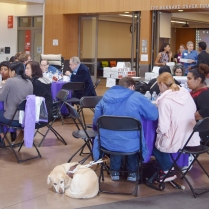 A crowd of people with disabilities sit around round tables and eat lunch