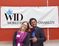 "A man and a woman pose in front a banner that reads ""WID"""