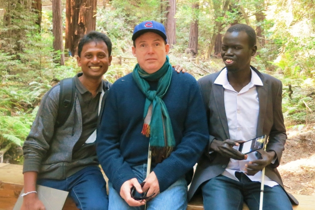 Three men pose in a forest
