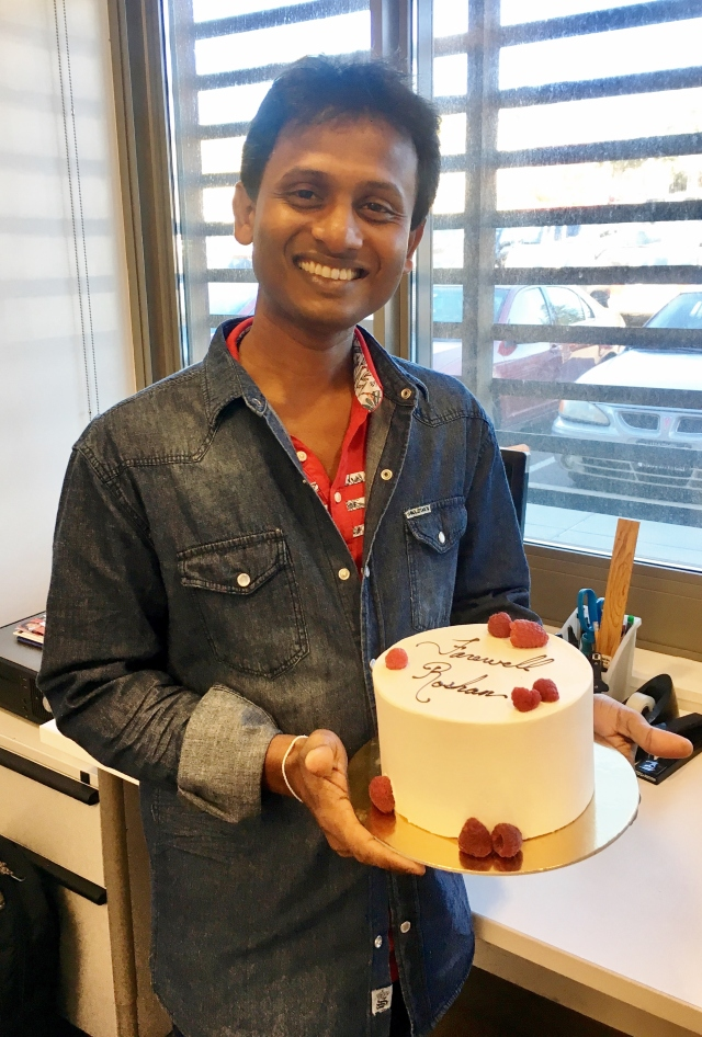 A young man smiles and holds a goodbye cake