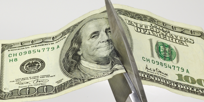 Image of scissors slicing through a $100 bill