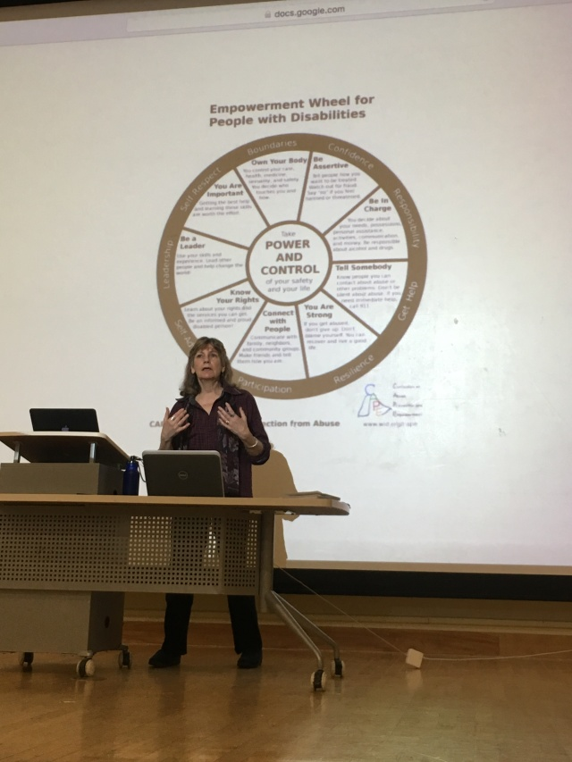 A woman stands on stage with a wheel of power and control projected behind her