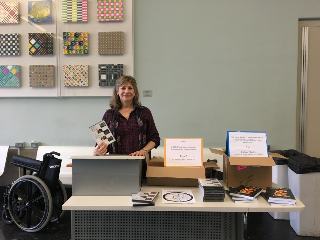 Link to Dr. Saxton Delivers Keynote at Sexual Violence Conference article; image of a woman standing at a desk, displaying books and DVD cases