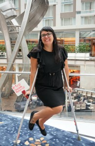 """A woman on crutches poses with a whiteboard that says, """" #Krip Chicana Feminist """""""