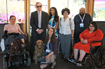 A group of seven people with varied disabilities and one service dog