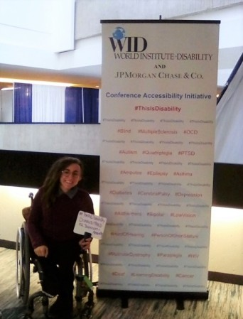 "A woman in a wheelchair poses in front of the This Is Disabilitiy sign and holds a whiteboard that says, "" #This Is Disability Disabled & Proud O.I. Depression & Anxiety """