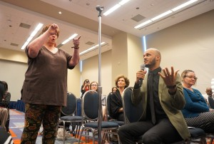 A woman signs to the panelists while a male ASL interpreter speaks her question into a microphone